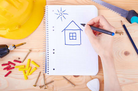 Hand drawing a house and different tools  on a wooden background  photo
