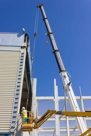 Lift for workers on metal girders at a new construction site against blue sky photo
