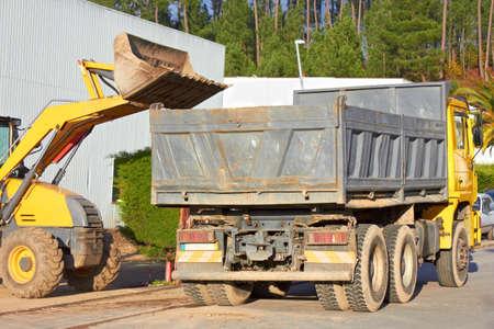 Graafmachine scoops een enorme emmer en is ongeveer om het te legen in de achterste lade van de vrachtauto