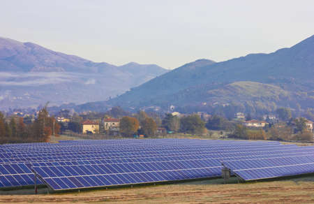 nonpolluting: Solar farm on a field against mountains
