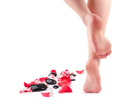 Female feet and Spa stones with rose petals isolated on white background