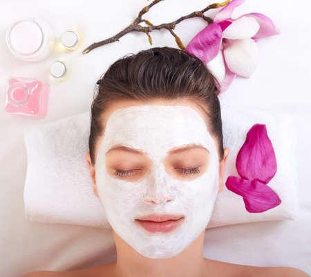 Mooi meisje ontvangen roze gezichtsmasker in spa beauty salon Stockfoto