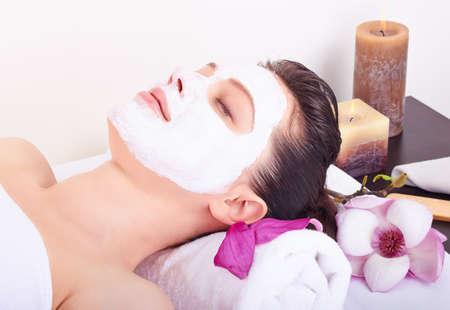 tratamiento facial: Muchacha hermosa joven que recibe la m�scara facial de color rosa