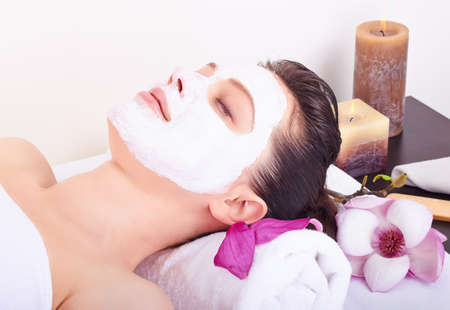 resting mask: Young beautiful girl receiving pink facial mask