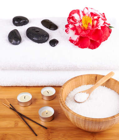 Spa setting with candles, flower, towel, salt and stones over white background  photo