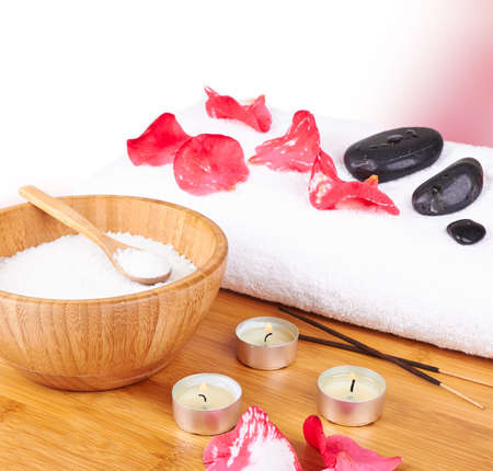 Spa setting with candle, flower red petals, towel and salt  on wooden background photo
