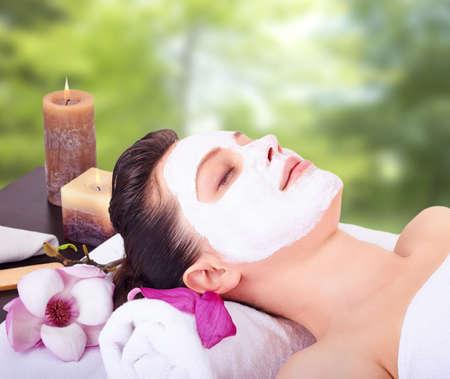 tratamiento facial: Muchacha hermosa joven que recibe la máscara facial de color rosa