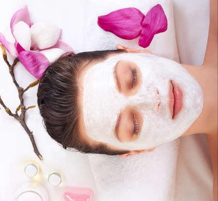 Young beautiful girl receiving pink facial mask in spa beauty salon