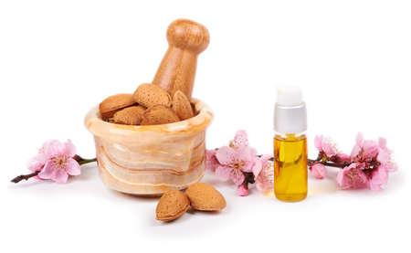 amandelolie en amandelnoten met bloemen op witte achtergrond Stockfoto