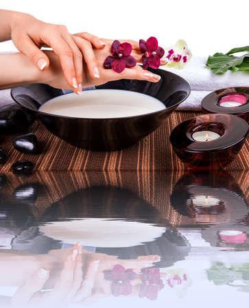 Vrouw handen met orchideeën en kom melk Stockfoto - 26370783