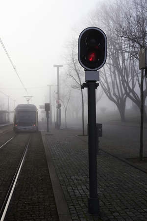 urban railway track with red signal light at foggy dusk