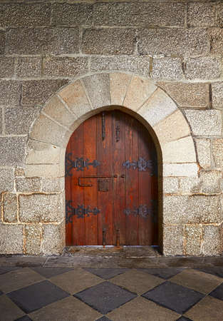 Ancient wooden door in old stone castle in Guimaraes, Portugal