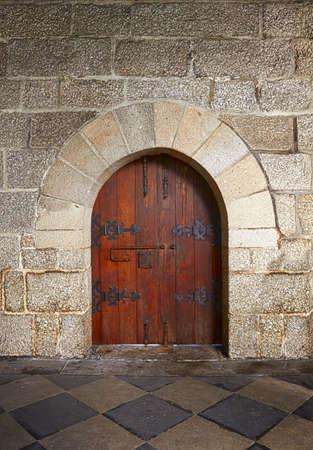 wooden facade: Ancient wooden door in old stone castle in Guimaraes, Portugal Editorial
