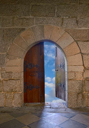 Door with arch opening to a beautiful cloudy sky