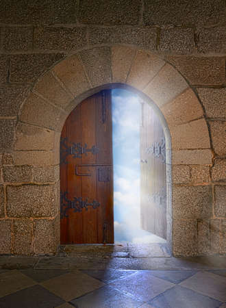 heavens gates: Door with arch opening to a beautiful cloudy sky Stock Photo