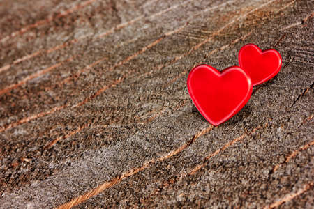 Two red hearts on old shabby wooden background photo