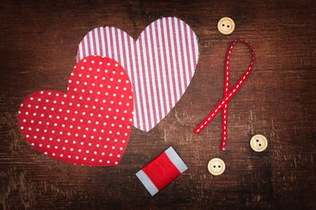 Textile hearts and buttons on old shabby wooden background photo