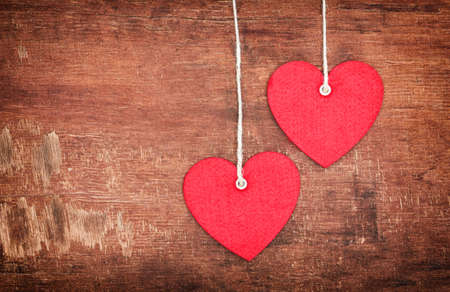 Two Textile pendent hearts on old shabby wooden background photo