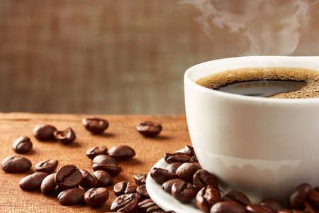 alubias: Taza de caf� y granos de caf� en la mesa