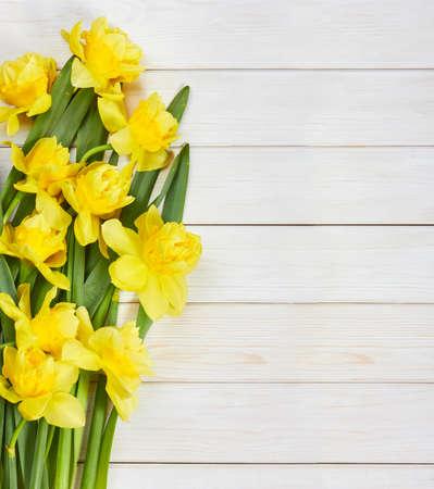 白い木製の背景の春水仙の花の花束