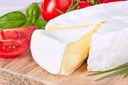 goat cheese: Queso de cabra, tomate cherry y albahaca en una tabla de madera