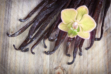 pod: Vanilla sticks and orchid flower on the wood background Stock Photo