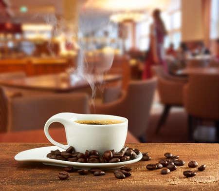 カフェのテーブルでホット コーヒーのカップ