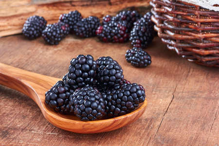 blackberry fruit: Blackberries in a spoon on wooden background
