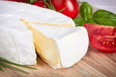 queso cabra: queso de cabra, tomate cherry y hierbas en una tabla de madera
