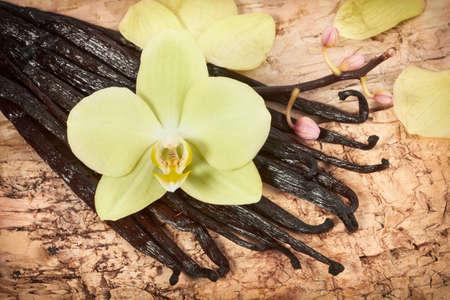 Vanille stokken en orchidee bloem op de houten achtergrond