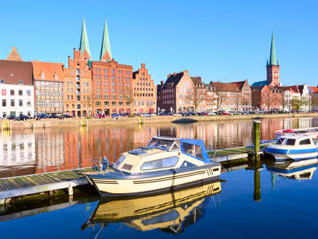 trave: Boats and Historic buildings at Trave river, old town of Lubeck, Germany Stock Photo