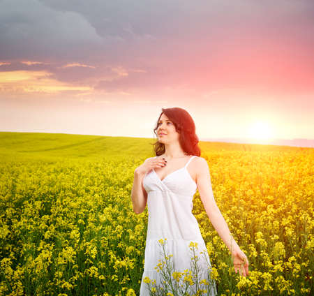 Woman in field with flowers at summer sunset. photo