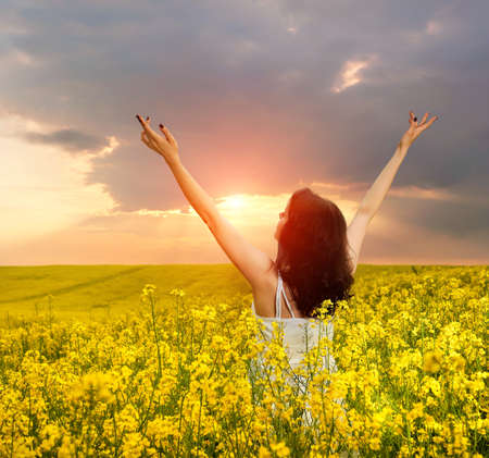 Woman in field with yellow flowers at summer sunset. photo