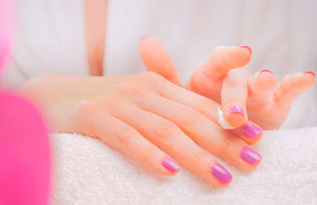 Application of cream on female hands with purple nail