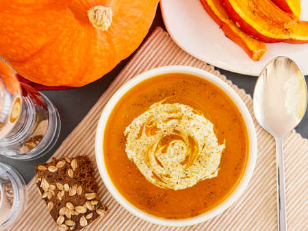 Pumpkin soup with cream on dark, Top view Stock Photo