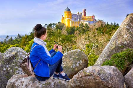 Woman traveler enjoying famous landscape and Palace of Pena, Sintra, Lisboa