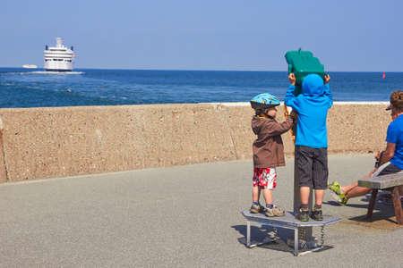TRAVEMUNDE, GERMANY - JUNE 11, 2013: Children looks on ships in telescope
