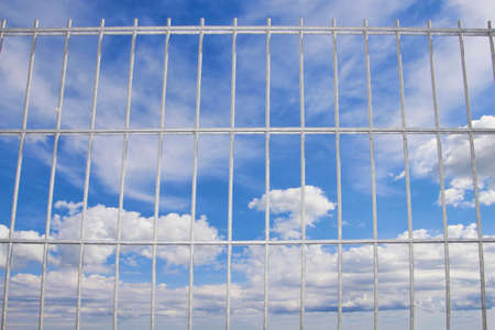 blue sky behind a wire lattice, looking through a wire up to the blue sky Stock Photo