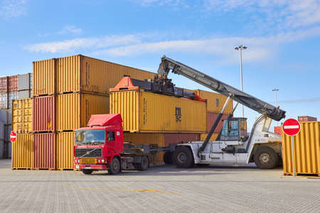 PORTUGAL, PORTO- FEBRUARY 05, 2013: Toplifter laying down cargo container on truck