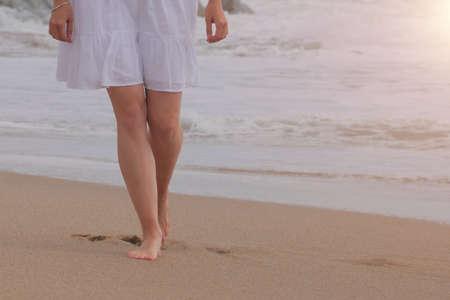 Woman in white dress walking on sand beach Stockfoto
