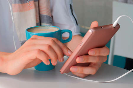 Female hands using smartphone. Cup of coffee