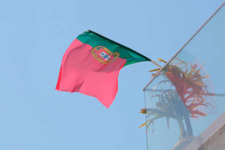 Portugal flag fixed on house balcony and fluttering on wind