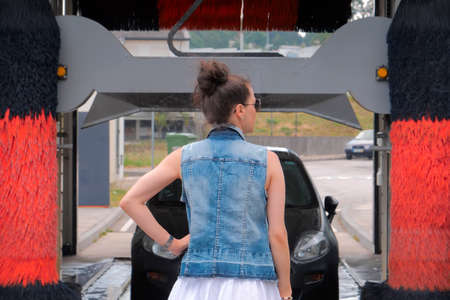 Woman standing back in front of car, car washing process Stockfoto