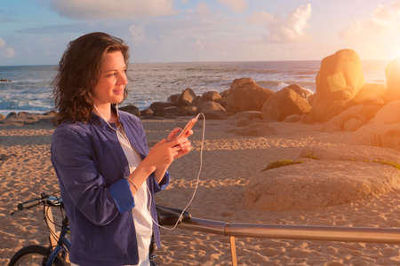 Beautiful woman in headphones listening to music and using smartphone Stockfoto