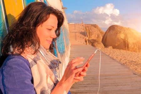 Smiling caucasian woman in headphones using smartphone