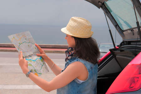 Caucasian woman near her car looking at road map Stockfoto
