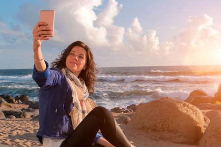 Beautiful caucasian woman taking selfie on smartphone on beach