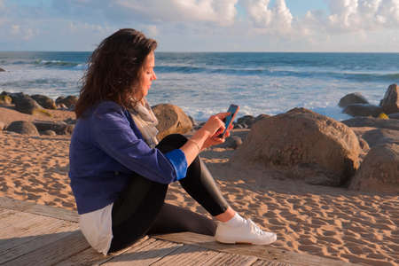 Beautiful black hair woman sitting on wooden embankment and using smartphone