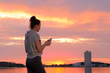 Caucasian woman in sport clothes using smartphone at sunset