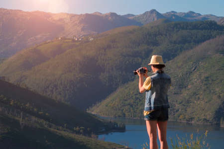 Female photographer in hat taking photo of green mountain and river